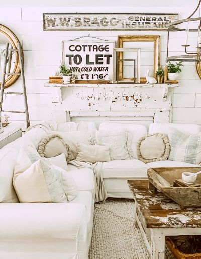 white sectional in living room with General Insurance sign hanging on shiplap wall