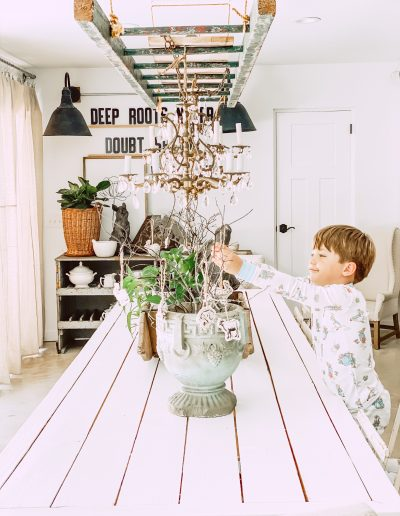 Harrison helping with twig arrangement on long white table in back room