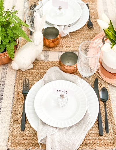Table setting with alabaster bunnies, black silverware and napkins