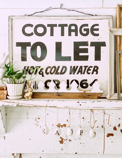 """""""Cottage to Let"""" vintage sign on white chippy mantel in living room"""