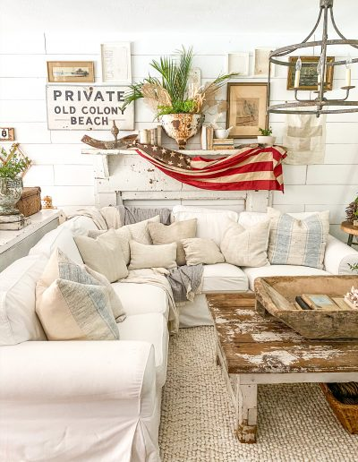 White sectional in front of mantel with vintage flag draped over it