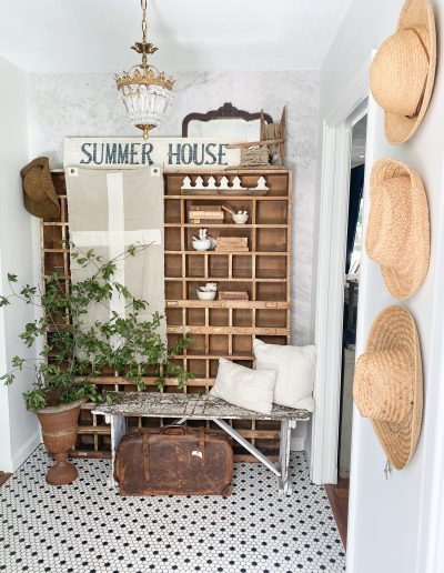Entryway with black and white penny tile flooring and three wicker hats